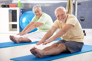 two seniors exercising on yoga mats