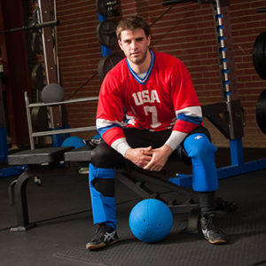 Photo of Matt Simpson dressed in his Team USA Goalball gear and sitting on a bench with a goalball in front of him