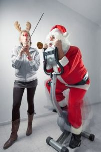 "Picture of ""Santa"" on a exercise bike with a lady with antlers on holding a stopwatch"