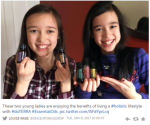 Picture of 2 young girls holding handfuls of Essential Oil bottles